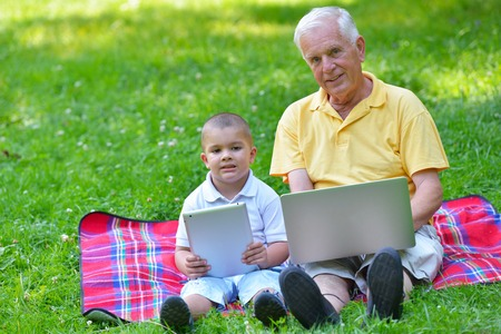 happy elderly senior grandfather and child in park using laptop computer photo