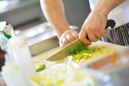 cocinando: Cocinero hermoso vestido con el uniforme blanco que adorna la ensalada de pasta y mariscos pescados en la cocina moderna
