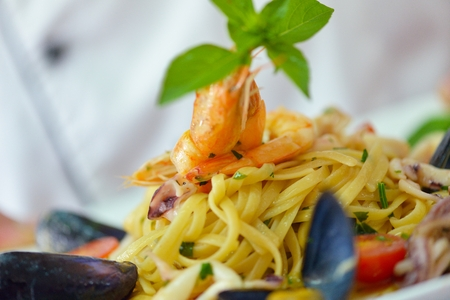 pasta salad: Handsome chef dressed in white uniform decorating pasta salad and seafood fish in modern kitchen