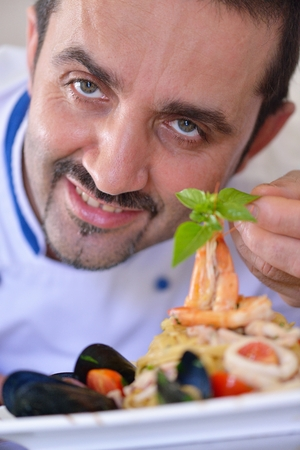 Handsome chef dressed in white uniform decorating pasta salad and seafood fish in modern kitchen photo