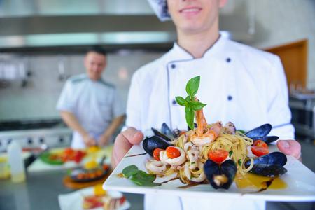 pescados y mariscos: Cocinero hermoso vestido con el uniforme blanco que adorna la ensalada de pasta y mariscos pescados en la cocina moderna