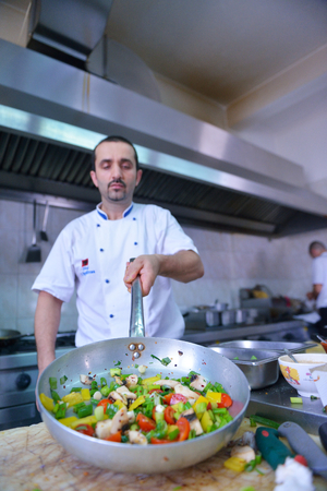 school of fish: Handsome chef dressed in white uniform decorating pasta salad and seafood fish in modern kitchen
