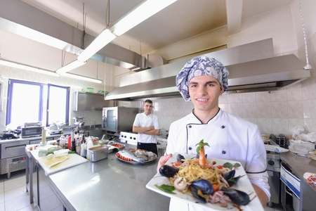hotel staff: Handsome chef dressed in white uniform decorating pasta salad and seafood fish in modern kitchen