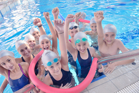 group of happy kids children   at swimming pool class  learning to swim Reklamní fotografie