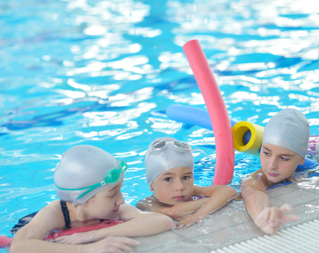 group of happy kids children   at swimming pool class  learning to swim photo