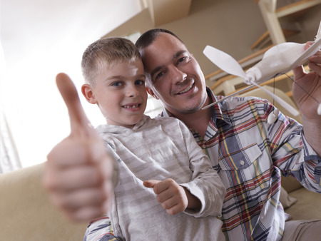 father and son assembling airplane toy at modern home living room indoor photo
