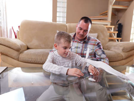 apoyo familiar: juguete padre e hijo avión montaje en casa moderna sala de estar interior