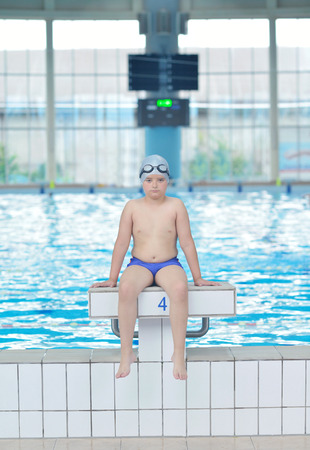 Fat kid: happy little child portrait on swimming school classes and recreation at indoor pool
