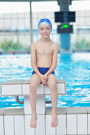 boy swim: happy little child portrait on swimming school classes and recreation at indoor pool