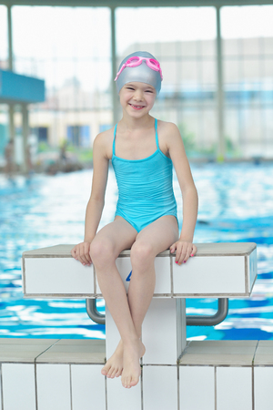 happy little child portrait on swimming school classes and\ recreation at indoor pool