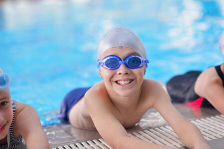 kids class: group of happy kids children   at swimming pool class  learning to swim Stock Photo