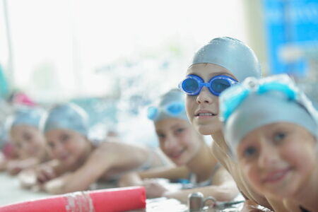 group of happy kids children   at swimming pool class  learning to swim Stock Photo