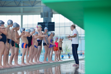 Fat kid: group of happy kids children   at swimming pool class  learning to swim Stock Photo