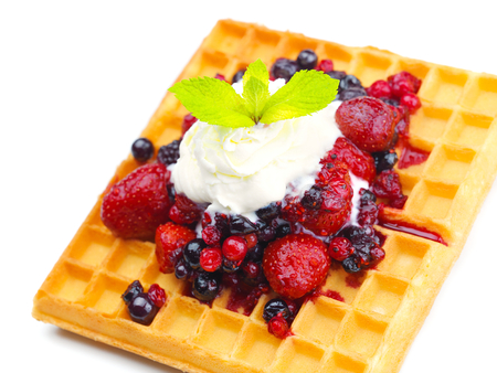 a selection of three italian gelato ice-cream scoops topped with nuts, chocolate, fruit served on crispy waffels photo