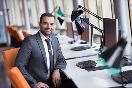 hombres guapos: feliz joven hombre de negocios retrato en la luminosa oficina moderna interior Foto de archivo