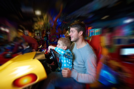 school playground: happy father and son playing driving wheel video game in playground theme park Stock Photo