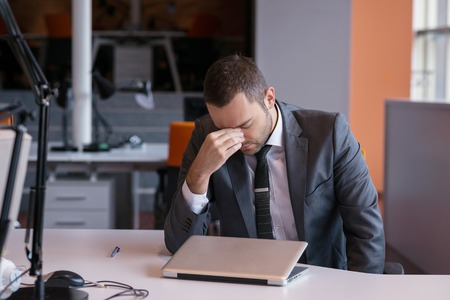 man working: frustrated young business man working on laptop computer at office