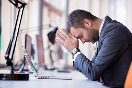 オフィスでラップトップ コンピューターで作業する不満の若いビジネス人