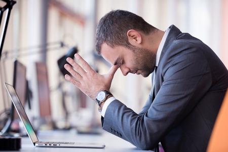 enojo: frustrado hombre de negocios joven que trabaja en la computadora port�til en la oficina