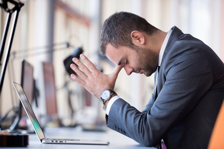 upset man: frustrated young business man working on laptop computer at office