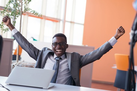 happy worker: Happy smiling successful African American businessman  in a suit in a modern bright office indoors