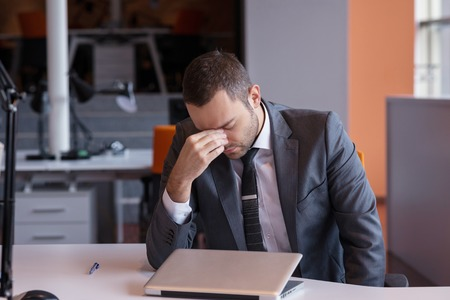 사무실에서 노트북 컴퓨터에서 작업 좌절 된 젊은 비즈니스 남자