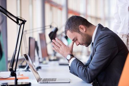 trabajo en la oficina: frustrado hombre de negocios joven que trabaja en la computadora port�til en la oficina