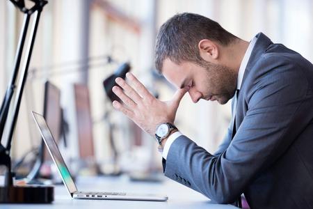 Frustrado hombre de negocios joven que trabaja en la computadora portátil en la oficina Foto de archivo - 36312620