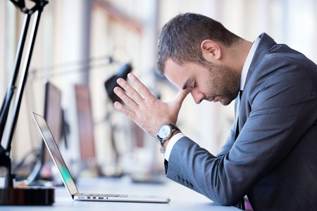 depressed man: frustrated young business man working on laptop computer at office
