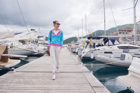 boat party: relaxed young woman walking in marina with yacht boats in bacground Stock Photo