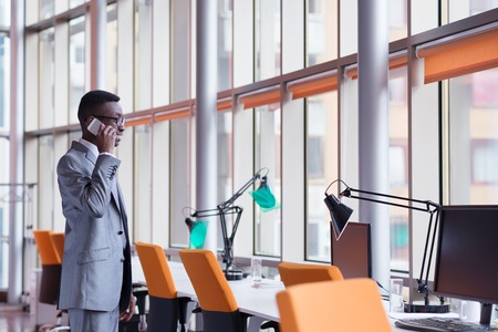 copy space: Happy smiling successful African American businessman  in a suit in a modern bright office indoors speel on phone