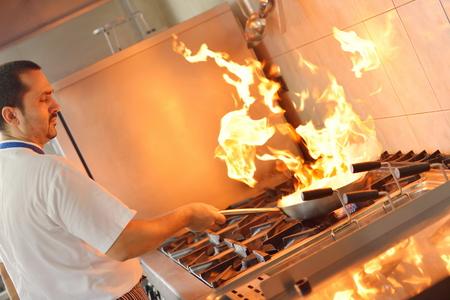 chef cocinando: Cocinero hermoso vestido con el uniforme blanco decoraci�n de ensalada de pasta y pescados mariscos en la cocina moderna