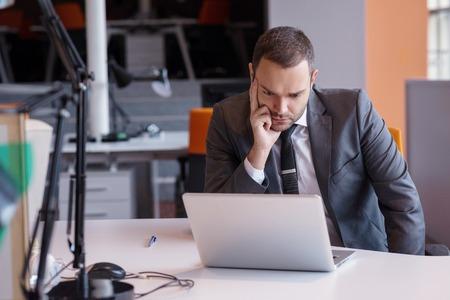 persona deprimida: frustrado hombre de negocios joven que trabaja en la computadora portátil en la oficina
