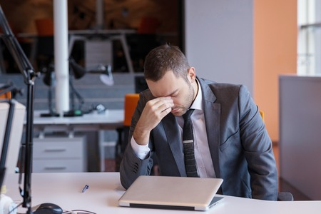frustrated student: frustrated young business man working on laptop computer at office