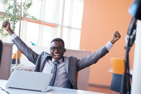 Gelukkig lachend succesvolle Afro-Amerikaanse zakenman in een pak in een moderne lichte kantoor binnen