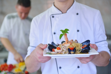 commercial kitchen: Handsome chef dressed in white uniform decorating pasta salad and seafood fish in modern kitchen