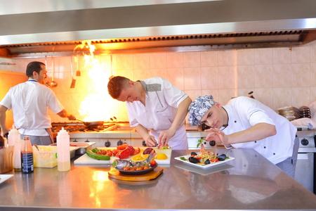 Cocinero hermoso vestido con el uniforme blanco decoración de ensalada de pasta y pescados mariscos en la cocina moderna Foto de archivo - 36324320