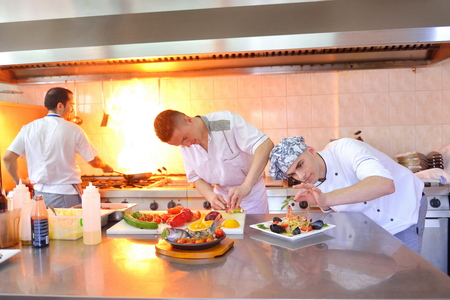chef kitchen: Handsome chef dressed in white uniform decorating pasta salad and seafood fish in modern kitchen
