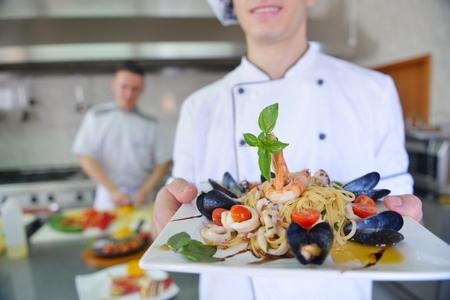Knappe chef-kok in het wit gekleed uniform decoreren pastasalade en zeevruchten vis in moderne keuken Stockfoto