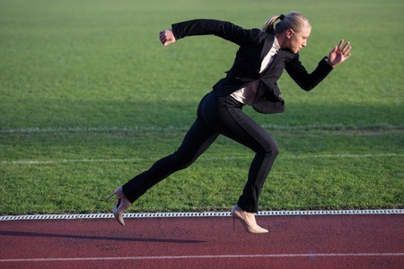 business woman in start position ready to run and sprint on athletics racing track Фото со стока