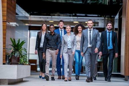 立っているとトップを歩いて若い多民族のビジネス人々 グループ