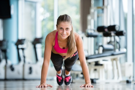 push people: Gorgeous blonde woman warming up and doing some push ups a the gym Stock Photo