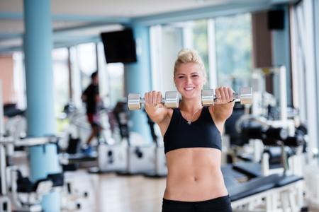 levantar pesas: Gorgeou chica mujer levantando unas pesas y trabajar en sus bíceps en un gimnasio