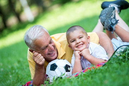 happy grandfather and child have fun and play in park on beautiful  sunny day photo