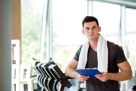 personal training: Portrait of a smiling male trainer with clipboard standing in a bright gym