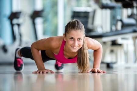 Gorgeous blonde woman warming up and doing some push ups a the gym 스톡 콘텐츠