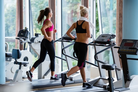 Beautiful group of young women friends  exercising on a treadmill at the bright modern gym Stok Fotoğraf