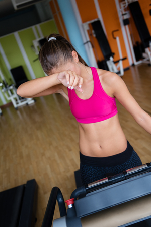tiring: Tiring woman exercising on treadmill in gym