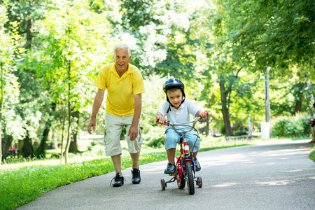 happy grandfather and child have fun and play in park on beautiful  sunny day