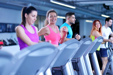 treadmill: group of young people running on treadmills in modern sport gym Stock Photo